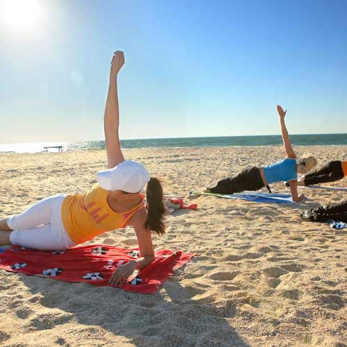 fitness camp clients stretching on the beach at weight crafters