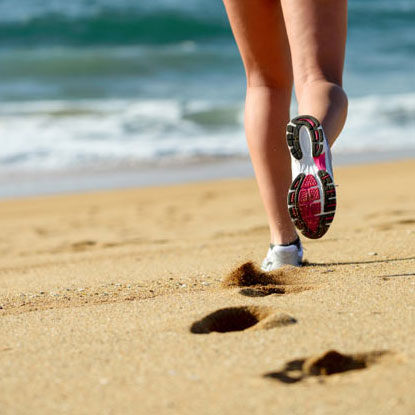 a woman runs on the beach