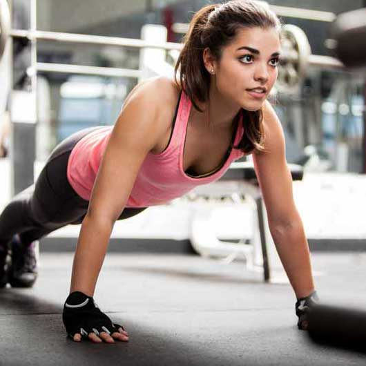 A young woman does a burpee