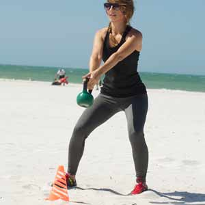 A trainer does kettle bell exercises on the beach