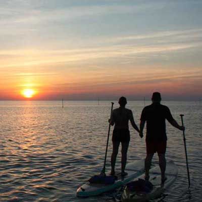 a happy couple paddleboarding at weight loss camp