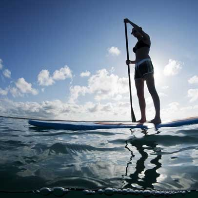 A young woman paddleboarding