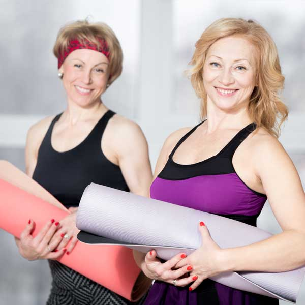 A couple of older women at Weight Crafters fat farm program with yoga mats.