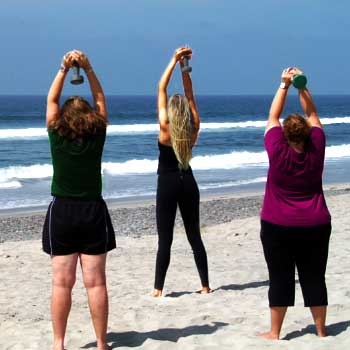 Three women work out on the beautiful Gulf Coast beach at Weight Crafters