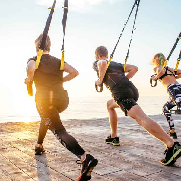 A group performs TRX exercises
