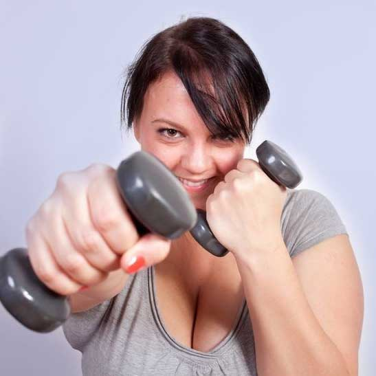 A female adult fat camp client using dumbells for exercise at Weight Crafters