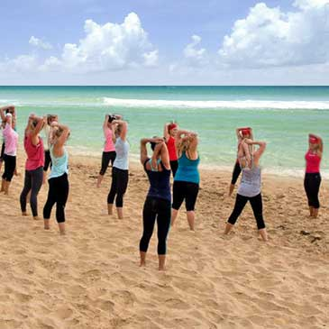 A larger group of weight loss campers stretch on the beautiful Gulf Coast beach.