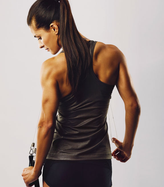 A fit woman flexes confidently after a session at Weight Crafters