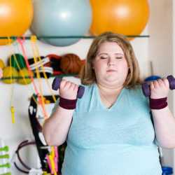 An obese female weight loss camp client exercising in our newly rennovated gym at Weight Crafters.