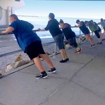 A group of weight loss campers stretching at the waters edge at Johns Pass